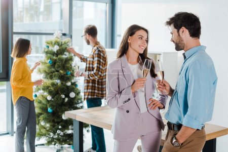 Photo for Selective focus of businessman and businesswoman with champagne glasses near multicultural colleagues and christmas tree - Royalty Free Image