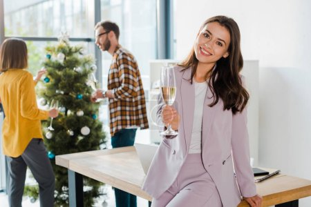 selective focus of attractive businesswoman smiling while holding champagne glass near coworkers and christmas tree