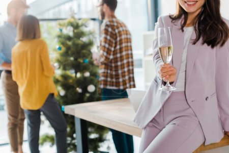 cropped view of businesswoman holding champagne glass near coworkers and christmas tree