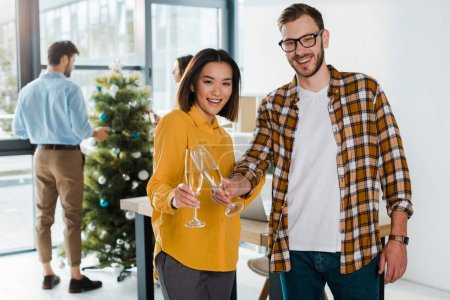 Photo for Selective focus of cheerful businessman and asian businesswoman toasting champagne glasses near colleagues and christmas tree - Royalty Free Image