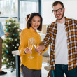 selective focus of cheerful businessman and asian businesswoman toasting champagne glasses near colleagues and christmas tree