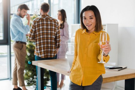 selective focus of happy asian woman holding champagne glass near coworkers and christmas tree in office