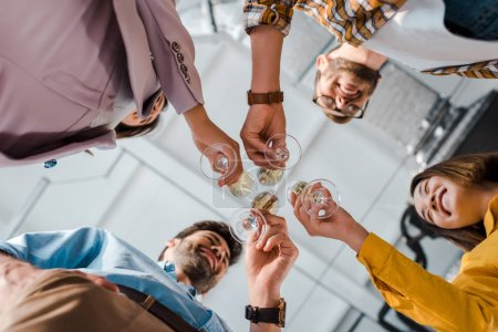 bottom view of cheerful businessmen and multicultural businesswomen toasting champagne glasses in office
