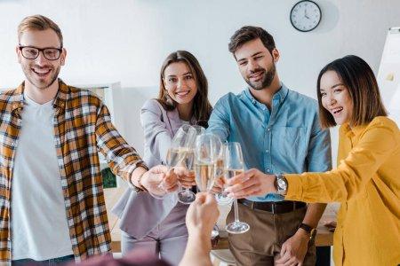 Photo pour Crochet vue d'un homme portant des verres de champagne avec des hommes d'affaires gentils et des femmes d'affaires multiculturelles au pouvoir - image libre de droit