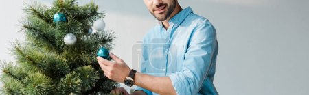 Photo for Panoramic shot of happy bearded man decorating christmas tree in office - Royalty Free Image