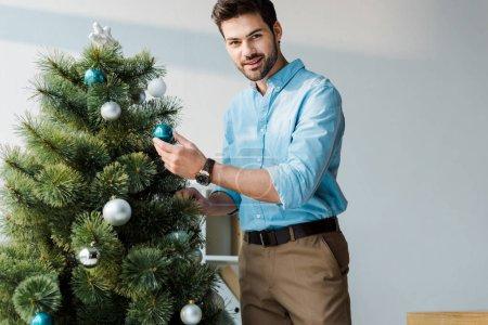 Photo pour Heureux homme barbu décoration arbre de Noël au bureau - image libre de droit