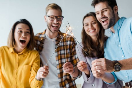 Photo for Selective focus of happy businessmen and multicultural businesswomen holding shiny sparklers in office - Royalty Free Image