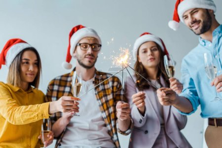 Photo for Selective focus of cheerful businessmen and multicultural businesswomen holding sparklers and champagne glasses in office - Royalty Free Image