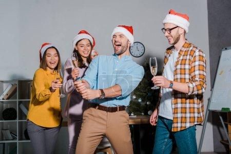Foto de Un hombre de negocios feliz en el sombrero de santa que sostiene el cracker del partido cerca de compañeros multiculturales con gafas de champán. - Imagen libre de derechos