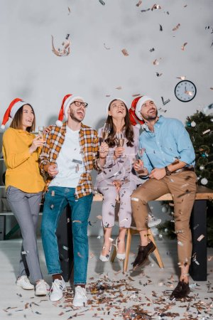 Photo for Happy businessmen and multicultural businesswomen in santa hats with champagne glasses near falling confetti - Royalty Free Image