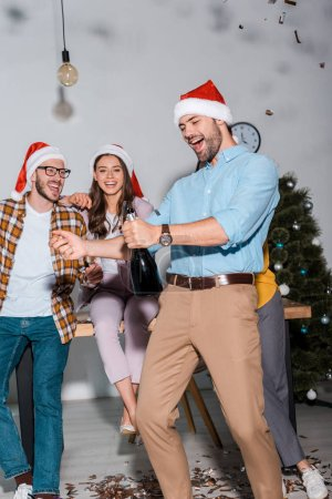 Photo for Happy businessman in santa hat holding champagne bottle near coworkers and falling confetti - Royalty Free Image