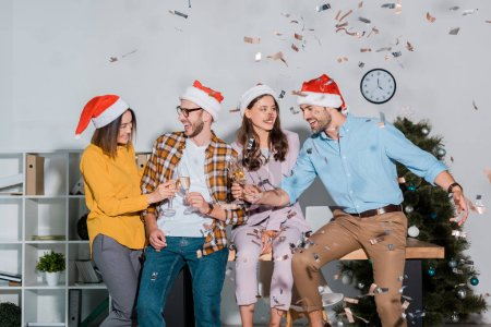Photo for Cheerful businessmen and multicultural businesswomen in santa hats toasting champagne glasses near falling confetti - Royalty Free Image
