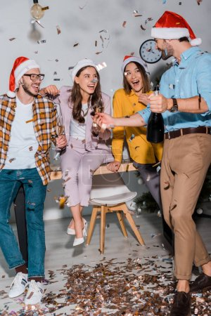 happy businessmen and multicultural businesswomen in santa hats with champagne glasses near falling confetti