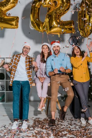 Photo for Happy businessmen and multicultural businesswomen in santa hats with champagne glasses near falling confetti and balloons with numbers - Royalty Free Image