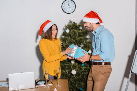 happy bearded businessman giving present to asian businesswoman in santa hat