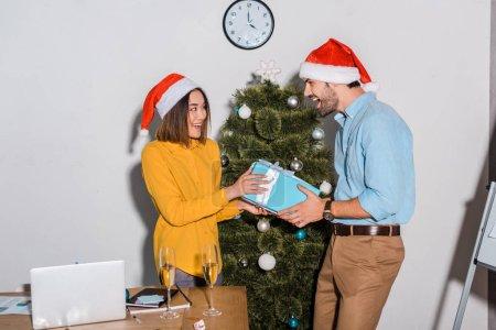 Photo pour Homme d'affaires barbu heureux donnant présent à une femme d'affaires asiatique en santa chapeau - image libre de droit