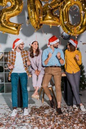 Photo pour Hommes d'affaires heureux et femmes d'affaires multiculturelles dans santa chapeaux près de confetti et ballons avec des chiffres - image libre de droit