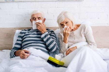 Foto de El marido enfermo y la esposa estornudan y tienen servilletas en el apartamento. - Imagen libre de derechos