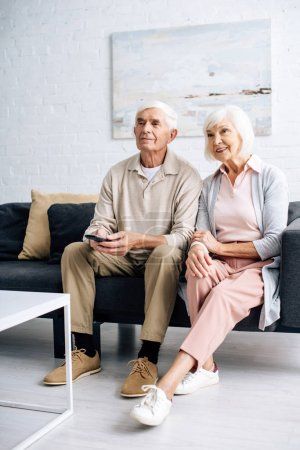 Photo for Smiling husband and wife watching tv and sitting on sofa in apartment - Royalty Free Image