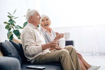 Photo for Side view of smiling husband and wife holding cups and sitting on sofa in apartment - Royalty Free Image