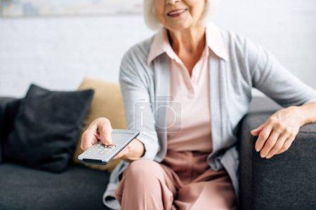 Photo pour Vue recadrée de femme souriante regarder la télévision dans l'appartement - image libre de droit