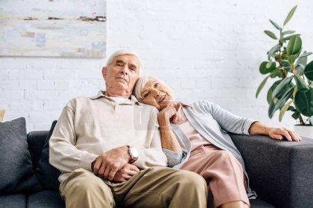 Photo pour Mari et femme souriante couché sur l'épaule et assis sur le canapé dans l'appartement - image libre de droit