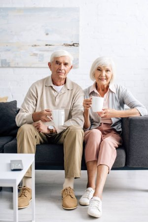 Photo for Smiling husband and wife holding cups and sitting on sofa in apartment - Royalty Free Image
