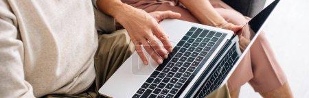 Photo pour Plan panoramique du mari et de la femme en utilisant un ordinateur portable dans l'appartement - image libre de droit