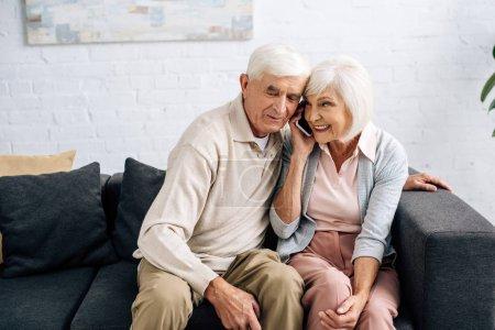 mąż i uśmiechnięta żona rozmawiają na smartfonie w mieszkaniu