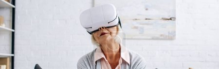 panoramic shot of senior woman with virtual reality headset in apartment
