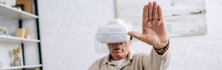 plano panorámico del hombre mayor en auriculares de realidad virtual con la mano extendida en el apartamento