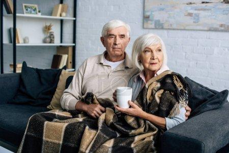 Mann und Frau mit Tasse auf Sofa sitzend und in Wohnung wegschauend
