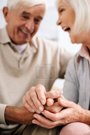 Photo for Selective focus of smiling husband and wife holding hands in apartment - Royalty Free Image