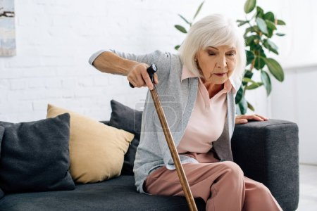 Photo for Senior woman with wooden cane sitting on sofa in apartment - Royalty Free Image