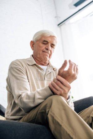 Photo pour Vue à angle bas de l'homme âgé assis sur le canapé et ayant mal à la main dans l'appartement - image libre de droit
