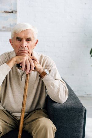 Photo for Senior man looking at camera and holding wooden cane in apartment - Royalty Free Image