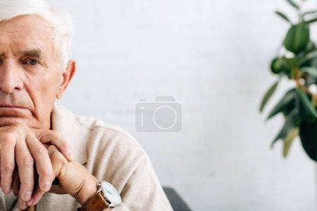 Photo pour Voir un homme âgé triste regarder une caméra et tenir une canne en bois dans l'appartement - image libre de droit