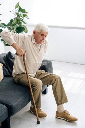 Photo pour Vue grand angle de l'homme âgé assis sur le canapé et tenant la canne en bois dans l'appartement - image libre de droit