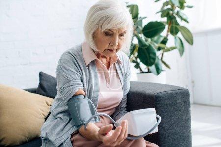 Photo pour Femme âgée assise sur le canapé et mesurant la pression artérielle dans l'appartement - image libre de droit