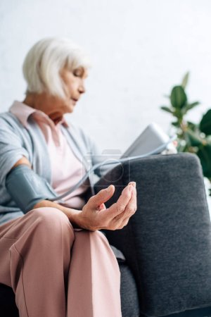 selective focus of senior woman sitting on sofa and measuring blood pressure in apartment