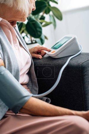 Photo pour Vue recadrée de la femme âgée assise sur le canapé et mesurant la pression artérielle dans l'appartement - image libre de droit