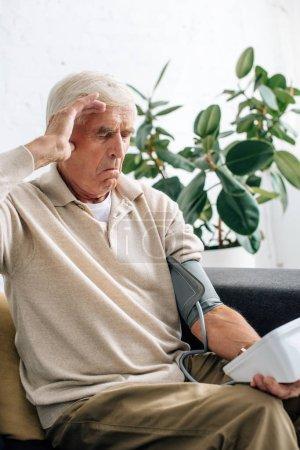 Photo pour Choqué homme âgé mesurant la pression artérielle et assis sur le canapé dans l'appartement - image libre de droit