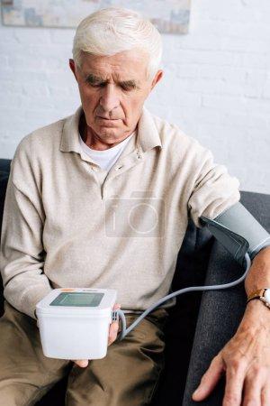 Photo pour Homme âgé mesurant la pression artérielle et assis sur le canapé dans l'appartement - image libre de droit