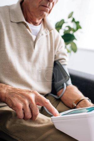 Photo pour Vue recadrée de l'homme âgé mesurant la pression artérielle et assis sur le canapé dans l'appartement - image libre de droit
