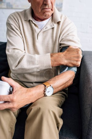 Photo for Cropped view of senior man measuring blood pressure and sitting on sofa in apartment - Royalty Free Image