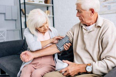 Photo pour Femme portant un tensiomètre sur le mari dans l'appartement - image libre de droit