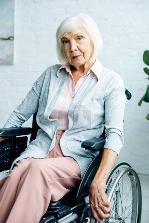 Photo pour Senior femme assise en fauteuil roulant regardant la caméra dans l'appartement - image libre de droit