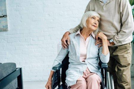 Photo pour Vue recadrée de mari étreignant femme attrayante en fauteuil roulant - image libre de droit