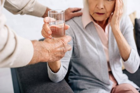 Photo for Cropped view of husband giving glass of water to wife with headache in apartment - Royalty Free Image