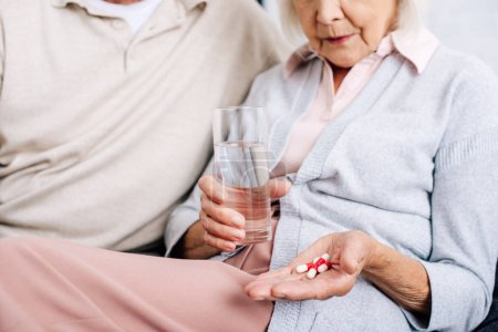 Photo for Cropped view of husband and wife holding glass and pills in apartment - Royalty Free Image